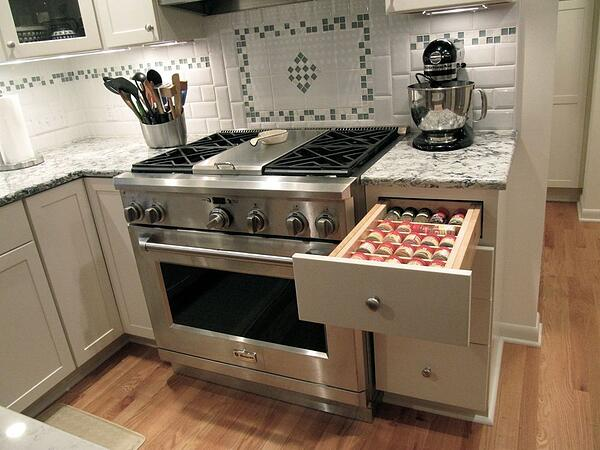 A Commercial Range and Hood with Nearby Spice Storage