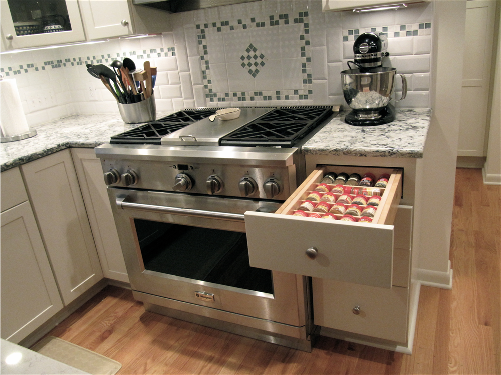 A dual fuel range with a hood that includes a warming shelf was a splurge for the cooks. Spices are located conveniently near the range. The backsplash is beveled white subway tile accented by glass and statuary marble mosaic tile.