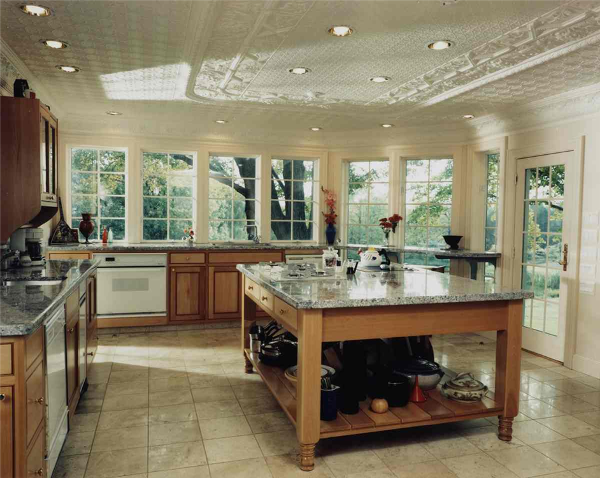 The wall of windows in this kitchen provides a view from any angle. The breakfast bar gives those seated an optimal view of the home's lovely garden and woods. Two people can easily cook in this space with two separate sinks, two cooktops and two dishwashers in this dual-fuel kitchen. If the view through the windows isn't enough, look up at the remarkable tin ceiling. The numerous coats of paint on the tin ceiling make it look as if it were original to the home.