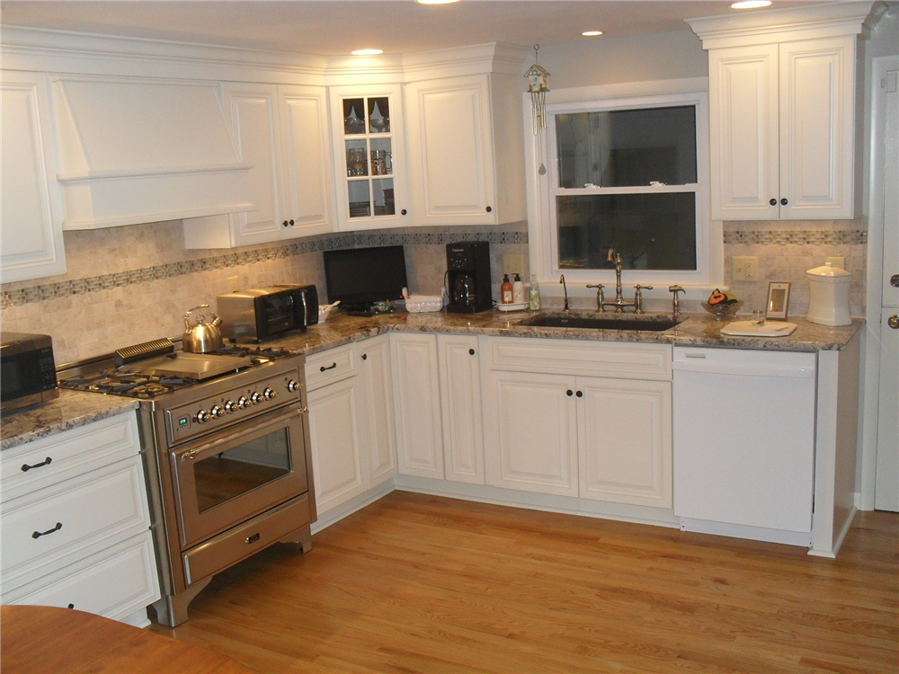 Silgranite sink with two-handle faucet, commercial gas range, granite countertops and white painted Jim Bishop cabinetry.