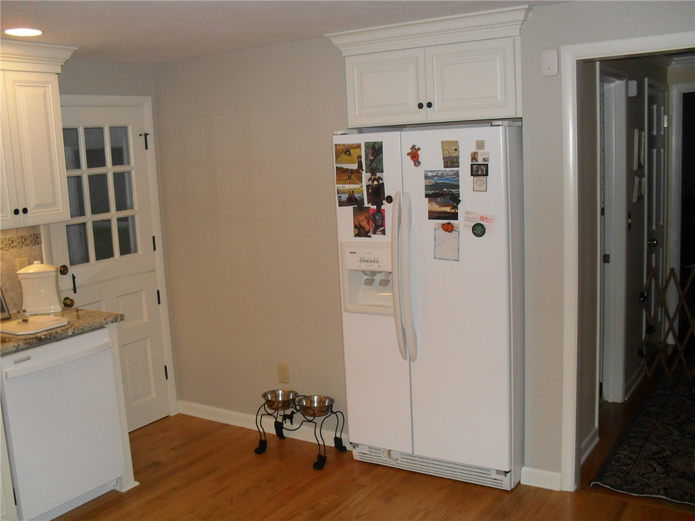 To meet the homeowner's need for more space and better traffic flow, a small closet off the kitchen was converted into space for a recessed refrigerator.