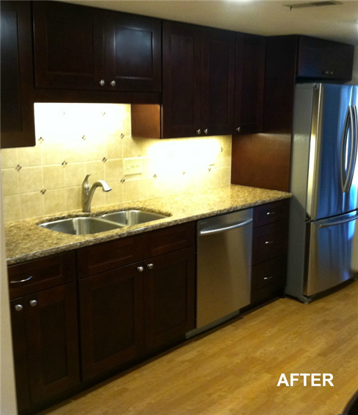The homeowners upgraded the original oak cabinets with dark stained Shaker cabinets from Jim Bishop Cabinets. The laminate countertops were replaced with quartz countertops from Cambria and accented with a new tile backsplash. Upgraded stainless steel appliances were added to update the look.