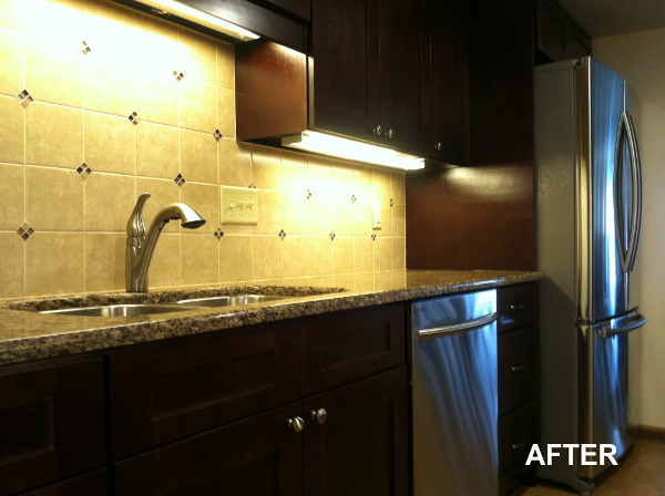 The tile backsplash includes glass accent tile to add sparkle and contrast to the dark cabinets and stainless steel sink.