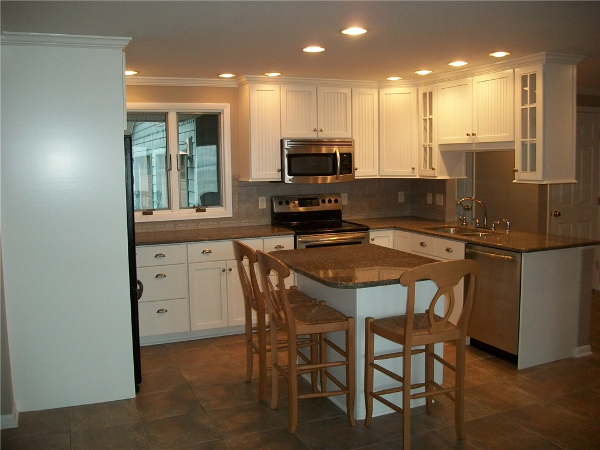 This kitchen remodel included new white beaded door cabinetry with quartz countertops, a new tile 12x12 tile floor, stainless steel appliance and new recessed lighting.