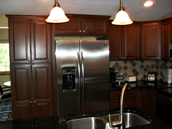 A divider wall was removed to create space for a tall kitchen cabinet to provide pantry space. The cabinets were topped with crown molding to create an illusion of height and add architectural interest to the room.