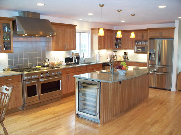 The kitchen features high sheen cherry cabinets, glass and metallic tile backsplash, an under cabinet wine refrigerator and granite countertops.