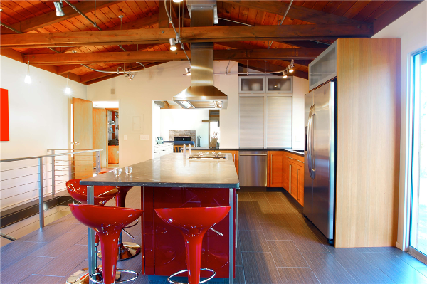 This award-winning kitchen features a bright red island with jet-black granite surface. Cabinetry includes an aluminum tambour garage with exotic wood grain perimeter cabinets. The cable railing system, aluminum exhaust hood and unique cabinetry give this kitchen an updated, contemporary feel.