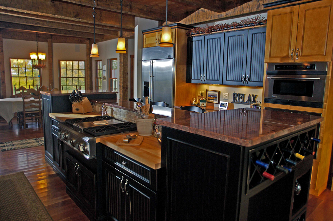 This elegant rustic kitchen combines distressed painted cabinetry with natural finished cabinets. A multi-level, multi-purpose island provides space for food prep, cooking and entertaining. Granite and butcher-block countertops provide style and functionality.