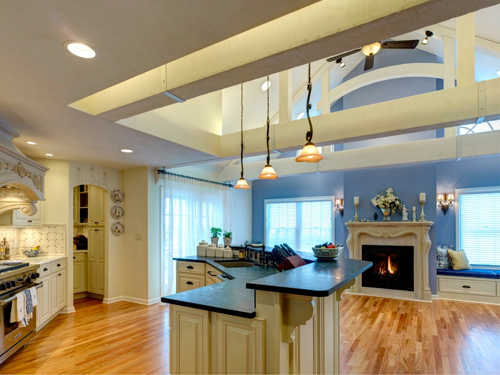 The design of the kitchen is French Country, which mixes decorative cabinetry and lighting, white wall tiles, rustic beams, marble and carved stone, and lavender blue accents.
