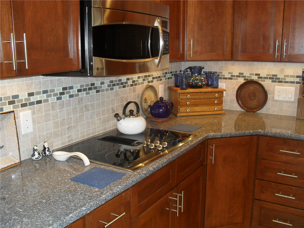The ceramic tile backsplash with a glass tile accent add color and function to this kitchen remodel.