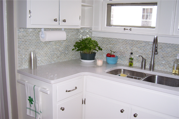 Adding new counters, a glass tile backsplash and painting the cabinets created a nice upgrade for this kitchen while staying within the customer's budget.
