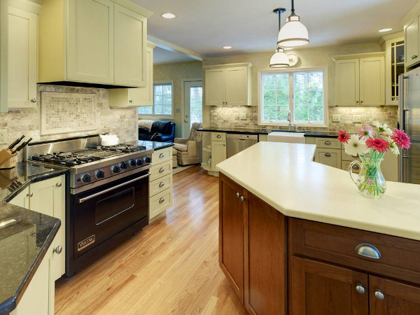 A Viking range and large area for food prep make this kitchen a perfect place for people who like to cook. Under cabinet lighting showcases the tumbled marble backsplash and granite countertops. The custom cabinet over the Viking range conceals the vent hood. The cherry island features Corian countertops.