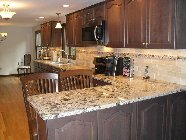 Granite tiles were used as an accent strip to tie the new backsplash into the granite kitchen counters.