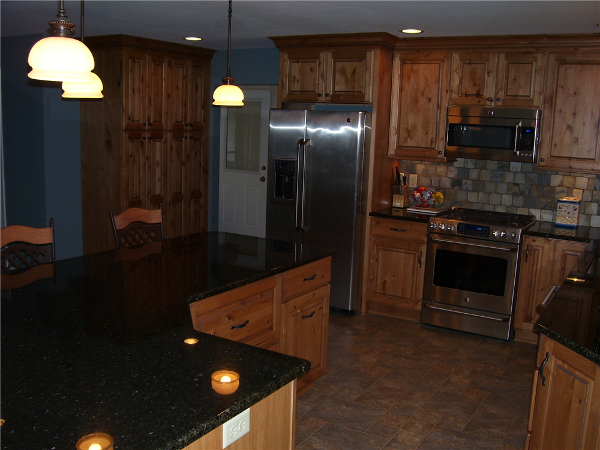 The polished granite counter on this island compliments the rustic wood species of the cabinetry.