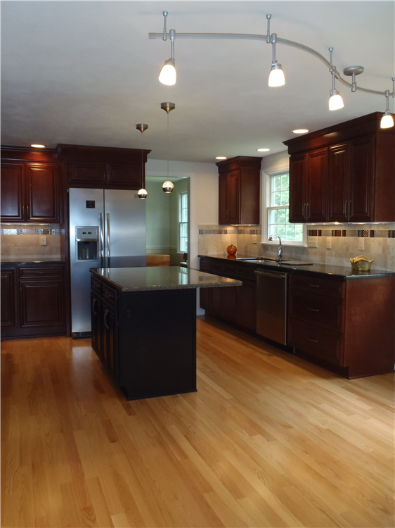 A modern track light provides both illumination and serves to separate the kitchen from the dining/living area in an open floor plan. Columns in the living room are made of the same material as the cabinets.
