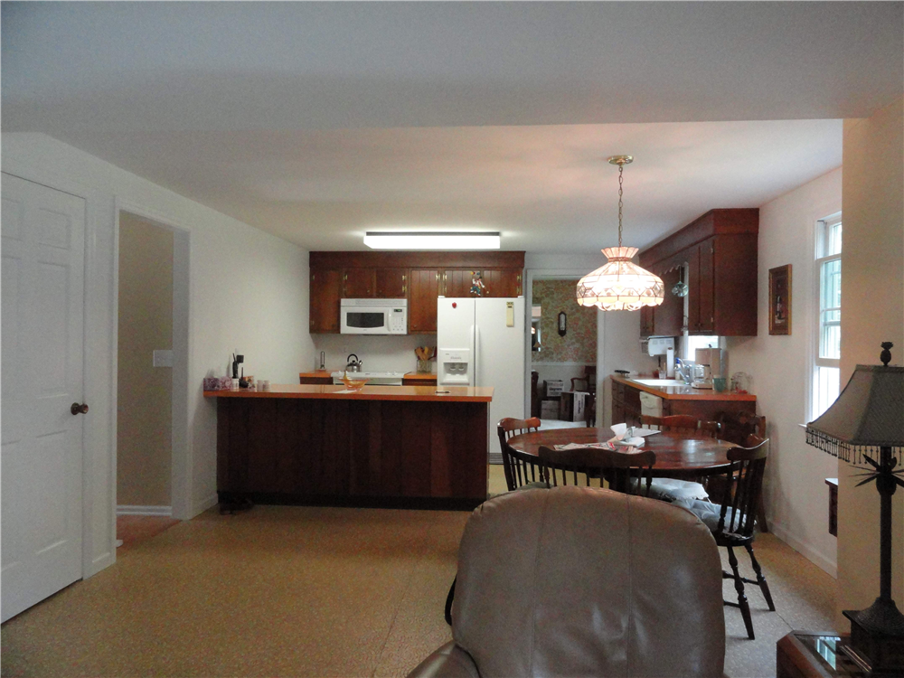 The kitchen before remodeling. The space was tight for preparing meals and there was little storage. A large fluorescent light provided primary illumination for the room. The linoleum flooring and laminate counters were out of date.