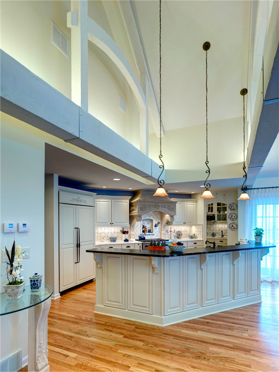 Among the outstanding features of this kitchen are its 15 ft. high cathedral ceiling and hand hewn interior trusses spanning the 24 ft. width of the room. There are many options for lighting including recessed, pendants and under-cabinet. Hidden uplights on the top of the wood beams light the cathedral ceiling.