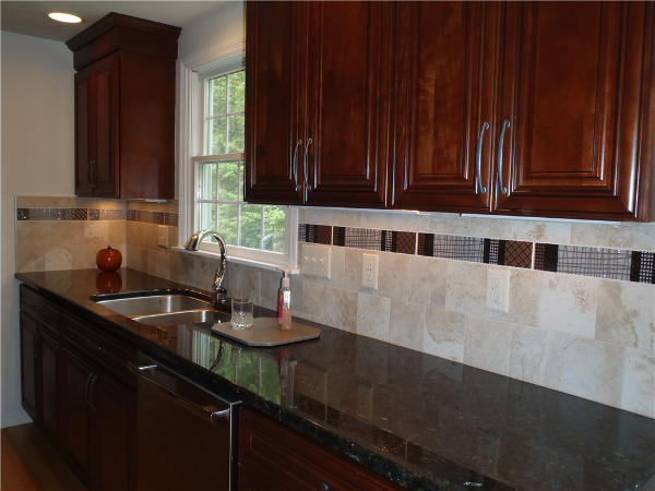 """Recessed and undercabinet lights provide task lighting on the counter areas. Backsplash field tiles are from Best tile. They are 6x6 Roman Travertine tiles in Silver and the accent tile is Dobkin Brown """"Matrix Listello"""". The backsplash adds both function and style to the kitchen."""