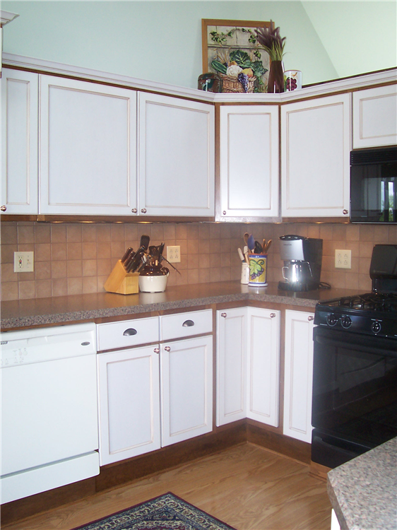 Changing the doors and hardware on these kitchen cabinets as well replacing the counters and backsplash gave this kitchen an entirely new look while keeping to the budget.