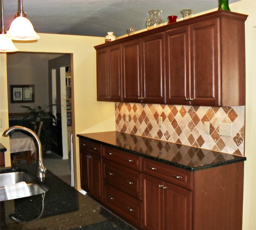 A black granite countertop with upper and lower cabinets and large deep drawers was added to provide storage for dishware, pots and pans, and utensils. The counter provides ample space and outlets for small appliances such as a mixer or crockpot.