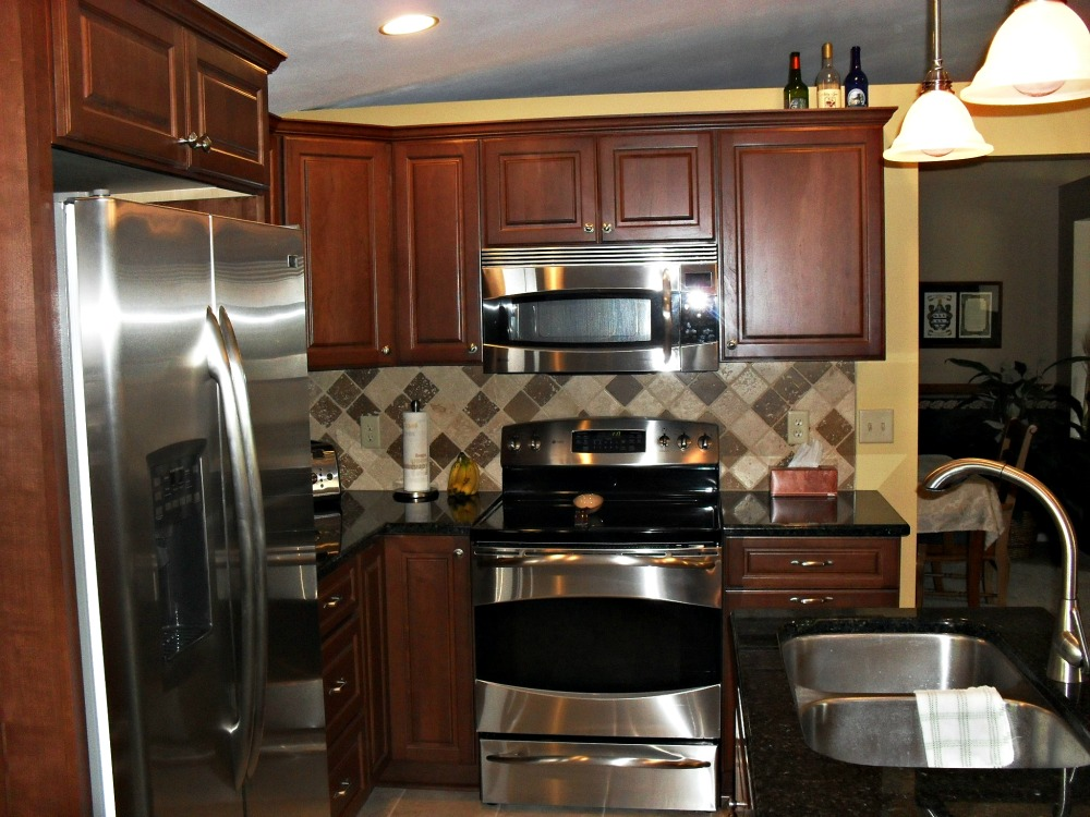 The updated appliances include a microwave/vent hood placed over the stovetop that conserves counter space and an Energy Star qualified refrigerator. A gooseneck faucet was added to the sink area to allow the cook to fill large pots with water.