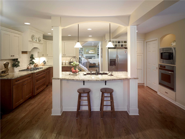 This exquisite kitchen features an island with two paneled posts and pendant lighting for food prep and dining. The posts not only complement the cabinetry but one conceals a load-bearing support. Other architectural features include an arch over the wall ovens, display shelving, crown moldings and a custom tile backsplash.