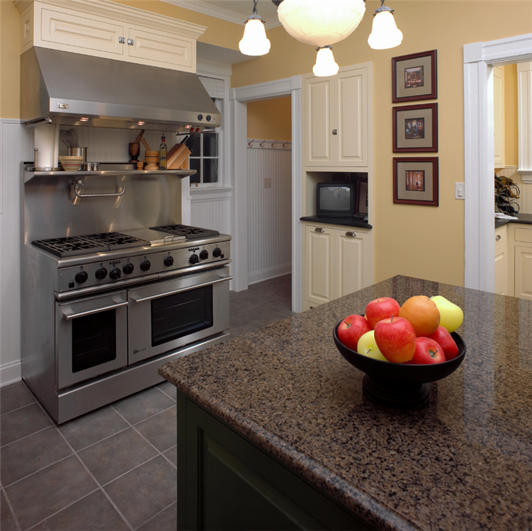 Deep colors and a clean, modern feel with custom built-in cabinetry, and a stainless steel commercial range and hood make this kitchen an ideal space for the culinary enthusiast.