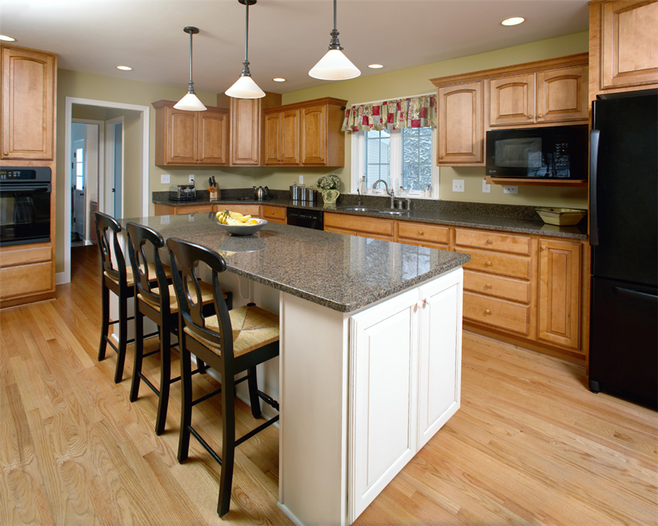 Very neutral, natural colors and woodwork make this kitchen feel comfortable, casual and relaxing, with new granite countertops, a large island, pendant lights and natural oak floors.