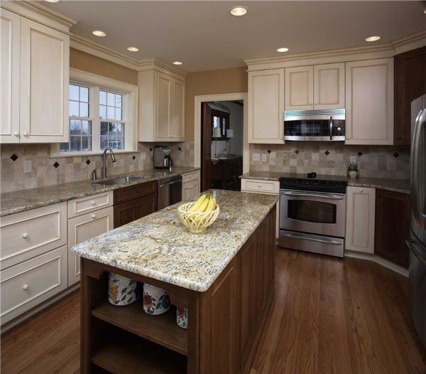 The granite surfaces in this kitchen on the island and counters provide ample workspace for the cook. The combination of painted and stained cabinetry accentuates the colors of the granite countertops and tile backsplash. Shelving at the end of the island creates space to store cookbooks and display pottery.
