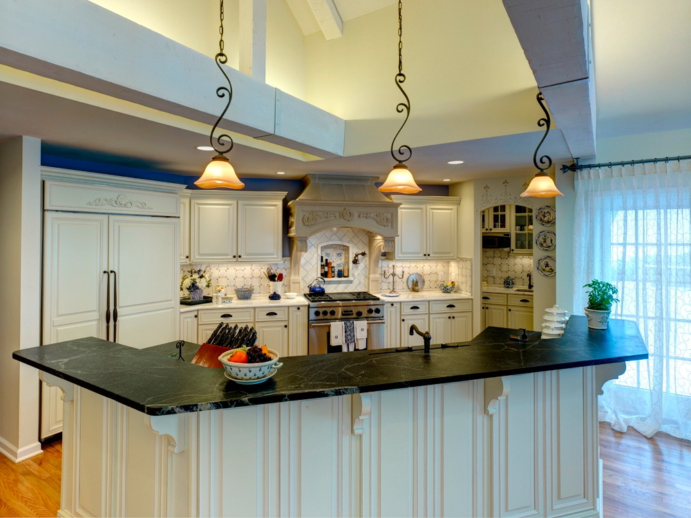 The kitchen has many amenities including a built-in refrigerator, commercial range, custom stone hood and a back area that includes a cafe bar. The cafe room is space that was set aside for the coffee machine, microwave and a small copper sink. The multi-functional island separates the kitchen and the great room.