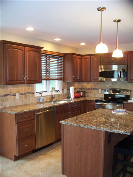 All aspects of this kitchen were updated from the stained maple cabinets, quartz countertops and tile backsplash with glass tile accent to the new lighting and appliances.