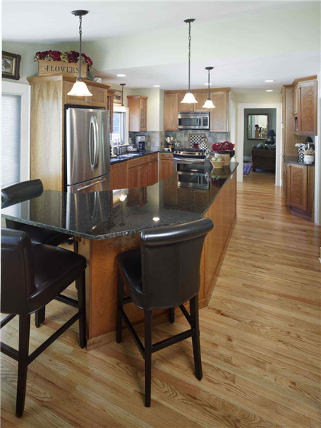 The oak cabinets of this kitchen blend well with the black solid surface countertops and island. The grey/blue backsplash includes a checkerboard pattern inset above the range. The very large island provides space for preparing meals and has an area for dining.
