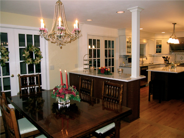 """The kitchen and dining room are adjoined by a peninsula that provides china storage in the dining room and space for three stools and for food prep on the kitchen side. The homeowners chose Jim Bishop """"Quakerstown"""" maple cabinets in a rich wood stain, """"Zinfandel"""" for the peninsula and island and painted """"Nordic White"""" finish for the kitchen perimeter cabinets. Cambria """"Torquay"""" quartz countertops, which looks like Carrera Marble, was selected for the island and peninsula."""