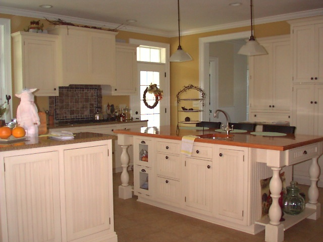 Painted cabinetry was installed with beadboard doors and drawer fronts. The large island features a prep sink and open storage on each end with large furniture style legs. Ceiling to floor cabinets provide ample storage space.