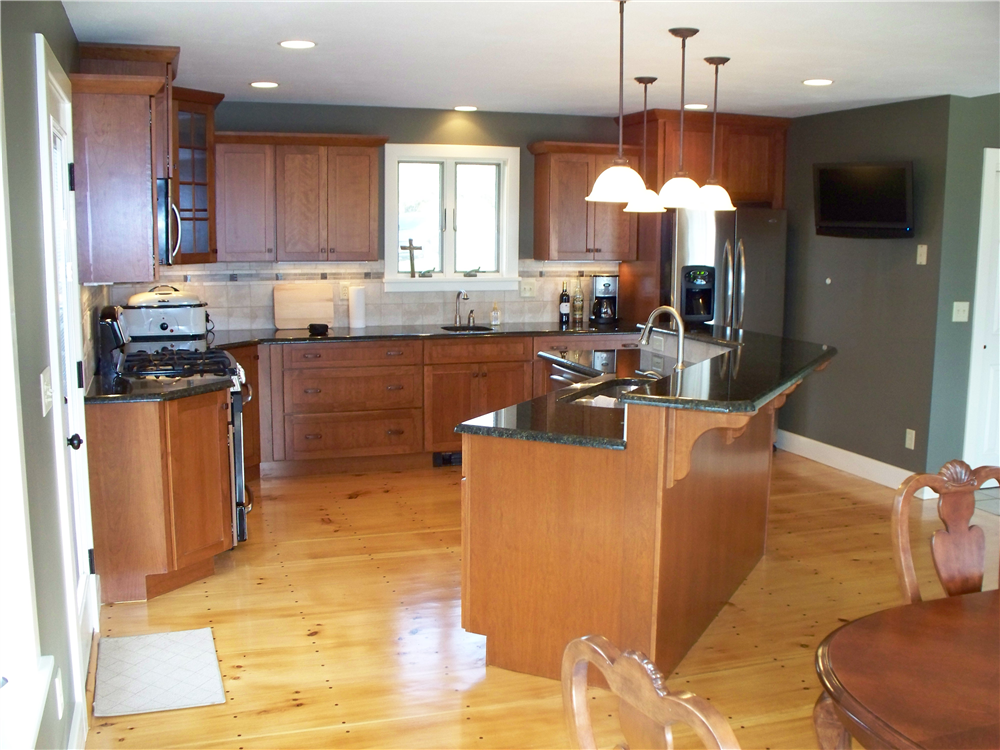 The two-tiered island set at an angle makes this kitchen functional and accessible from the surrounding spaces.