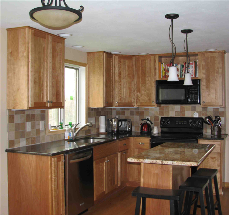 The graining in the cabinetry flows along with the veining in the granite giving the appearance of movement in this red birch kitchen.