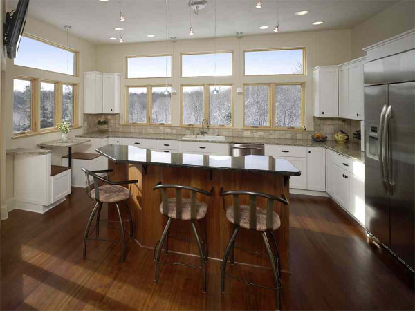 Large casement and transom windows bring in the outdoors. The small seating area built into the cabinetry provides space for quick meals while taking in the scenic views of the woods. A large island has additional seating oriented toward the view.