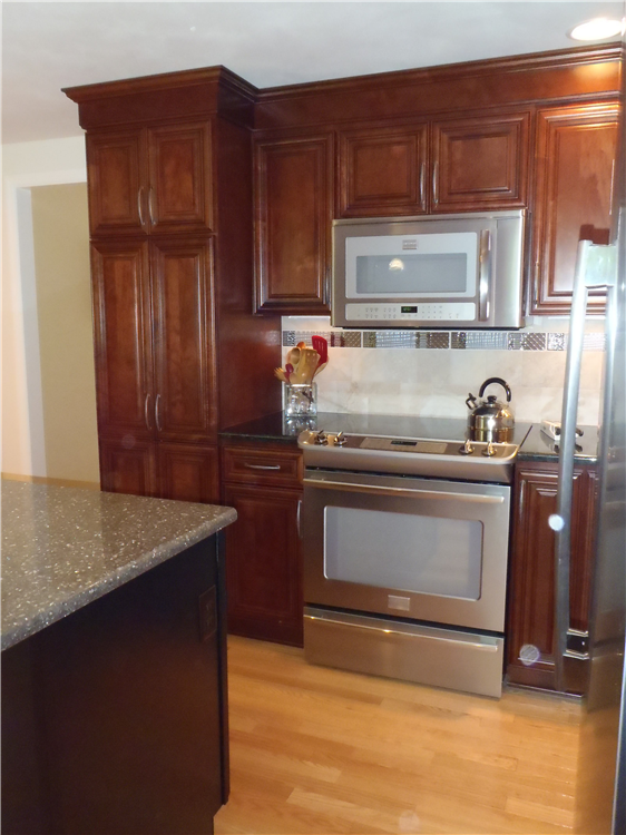 Updated appliances and new prefinished red oak flooring help to define the space and provide an interesting contrast to the rich wood stain of the cabinets and the sparkle of the backsplash.