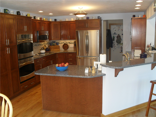 This kitchen features Jim Bishop flat panel cherry cabinets with quartz countertops.