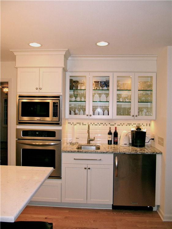 Wall ovens and storage for baking tins and pans are located near the island. The beverage bar has a bar sink and under cabinet refrigerator for drinks. Additional electrical outlets were added to the beverage for coffeemakers, and electric kettle and blenders.