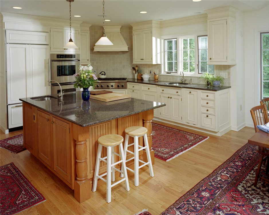 """This kitchen blends modern elements, such as the built-in refrigerator, with an """"Old World"""" feel established by a custom wood painted range hood and multi-piece crown molding on top of cabinets. The bold, contrasting island adds extra character, and functionality, to this space."""