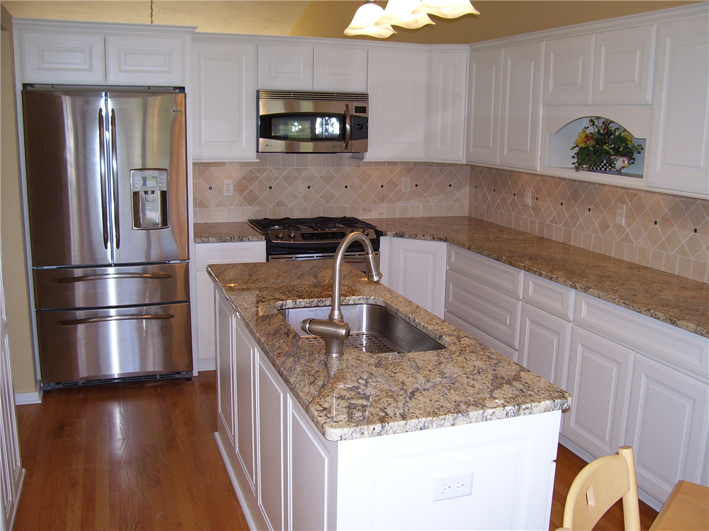The white cabinets and light colored stone counters brighten up this entire kitchen space.