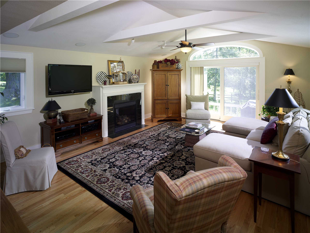 An eyebrow window was installed over a new sliding glass door in this family room allowing more light to come into the room and also creating the appearance of a larger room.