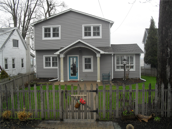 The exterior of this home was given a new look with an arched entry roof, vinyl siding and new windows.