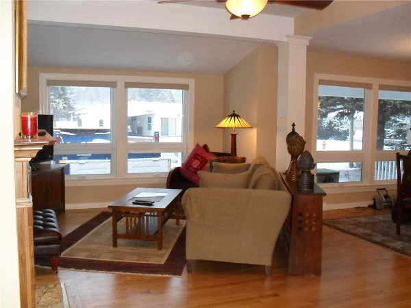 A car used to be parked in the location of the coffee table in this photo. Vinyl windows were installed in the location where the garage door once was. A second set of windows was also replaced as seen on the right side of the photo. From the street it looks as if the home never had a garage and that the windows are all original to the home.
