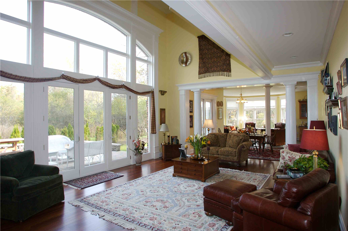 Swinging patio doors, fixed paneled windows and arch top widows make up this stunning wall of windows. Double hung windows can be seen in the rear sitting room with fixed transoms above.