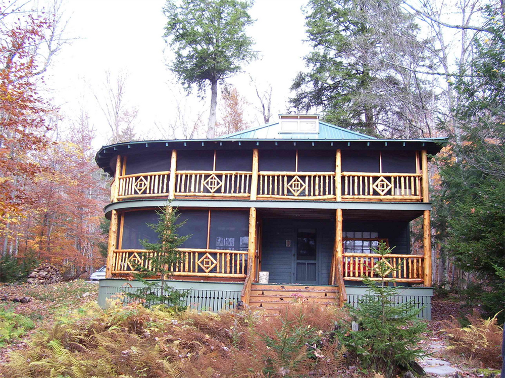 The rough-peeled cedar rail system on these porches give this Adirondack cottage a rustic look. The moose and tree cut-outs in the front stair stringers add character to the exterior.