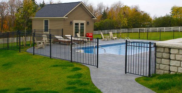 A custom pool house provides space for entertaining and storage. A Stampcrete sidewalk was installed from the deck of this home to the in-ground pool. Stampcrete also completes the patio area. Stampcrete is colored and imprints replicate the look of natural stone.