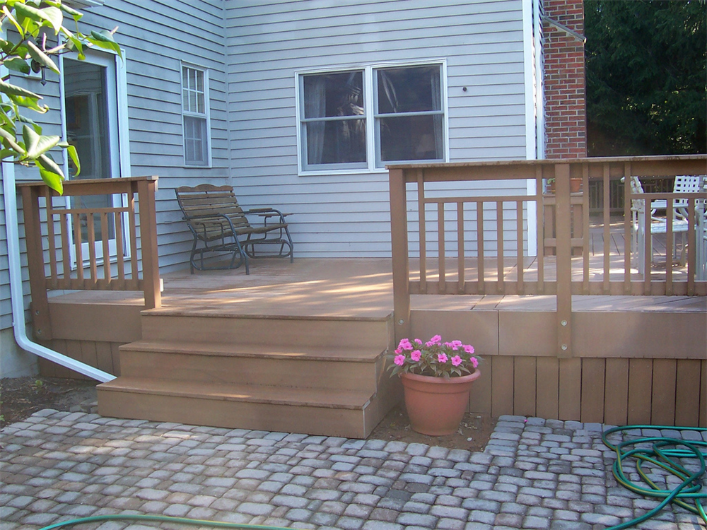 This composite deck features a custom composite rail design with composite skirting. The combination of the deck and the brick patio creates a large and relatively low maintenance exterior living space.