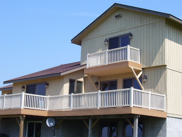 A maintenance-free vinyl deck system with brown deck boards and a white rail provide space for outdoor living.